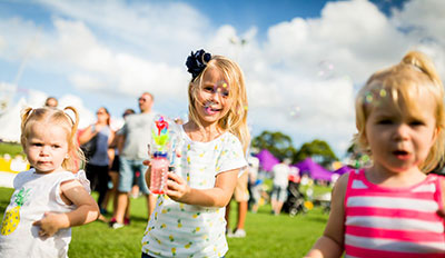 Three children enjoying themselves at an Australia Day event.